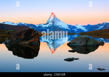view from a mountain lake at the Matterhorn with the top in reddish light, Switzerland, Valais - Stock Photo