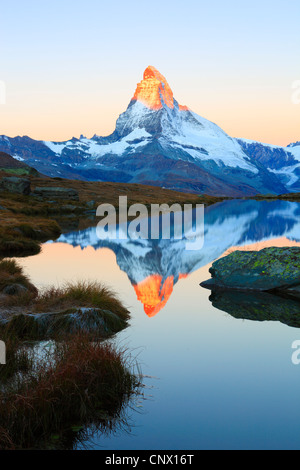 view from a mountain lake at the Matterhorn with the top in golden light, Switzerland, Valais - Stock Photo