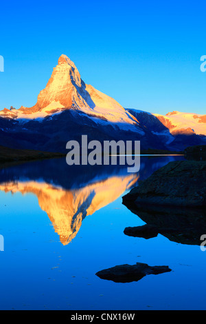 view from a mountain lake at the Matterhorn in golden light, Switzerland, Valais - Stock Photo