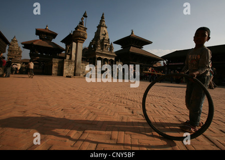 Nepalese boy plays with a pneumatic in Bhaktapur Durbar Square in Bhaktapur, Nepal. - Stock Photo