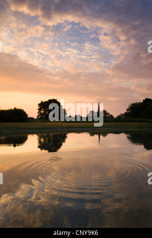 Salisbury Cathedral Spire and a beautiful dawn sky reflected in a rippled pond, Salisbury, Wiltshire, England. - Stock Photo