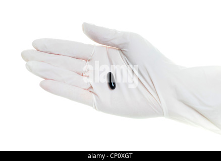 Gloved hand with black pills - Stock Photo