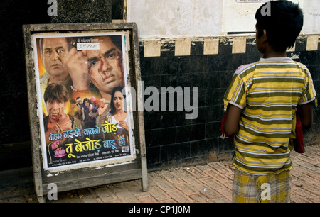 Boy watching the poster  in front of  cinema in Kolkata - Stock Photo