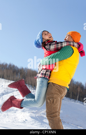 Young couple having fun in snow - Stockfoto