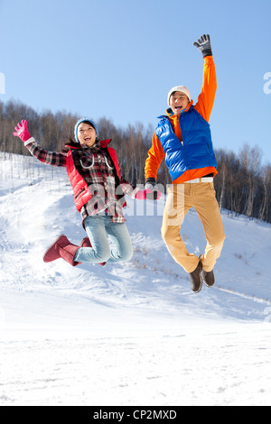 Happy young couple jumping in ski resort - Stockfoto