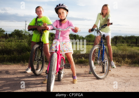 Three girls on a bicycles in rural area. - Stock Photo