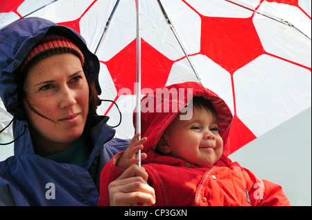 Mother and infant under an umbrella looking at the falling rain in a winter day . - Stock Photo