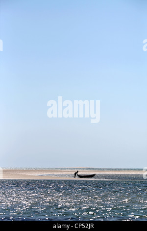 A Vezo malagasy boy and his dugout canoe at the sand banks of Belo-Sur-Mer, Western Madagascar, Africa - Stock Photo