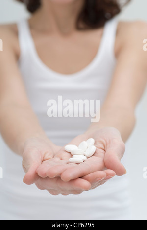 Mid adult woman showing white pills in hand - Stock Photo