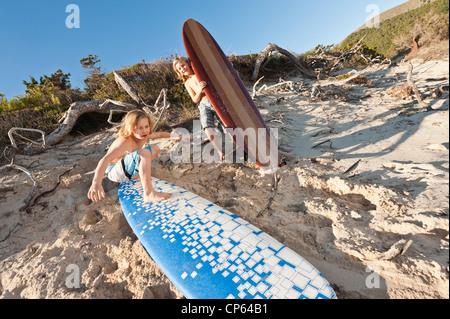 Spain, Mallorca, Children with surfboard on beach - Stock Photo