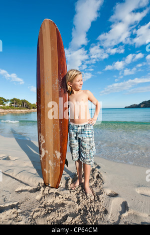 Spain, Mallorca, Boy with surfboard on beach - Stock Photo