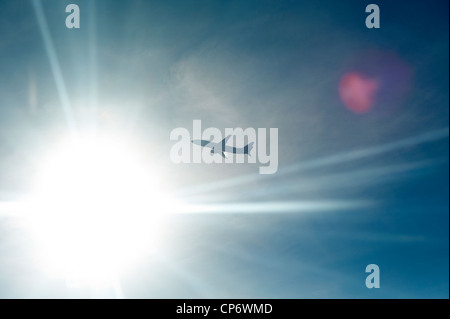An airplane backlit by the sun in midair - Stock Photo