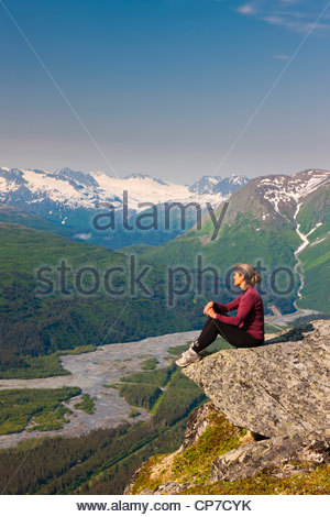 Hiker on rock outcrop in Thompson Pass overlooks Lowe River Valley, Chugach National Forest, Southcentral Alaska, - Stock Photo