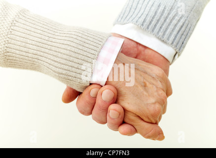 Seniors holding hands indicating their commitment to each other - Stock Photo