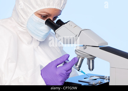 Photo of an embyologist examining a sperm sample through a stereo laboratory microscope - Stock Photo