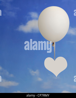 white heart shape hanging onto a white balloon against a blue sky with clouds - Stockfoto