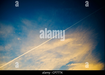 Commercial airline jet contrails across a clear dusk sunset blue sky - Stock Photo