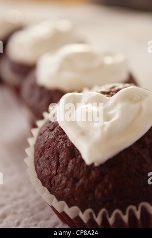 Valentine day themed red velvet cupcakes with heart shaped cream cheese topping. The romantic gifts are arranged - Stock Photo