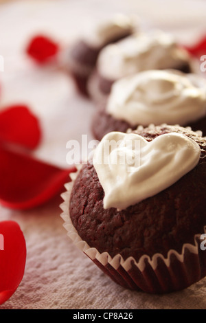 Valentine day themed red velvet cupcakes with heart shaped cream cheese topping. Rose petals are seen in the background - Stock Photo
