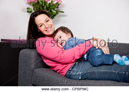 A mother cuddling her baby son on a sofa - Stock Photo