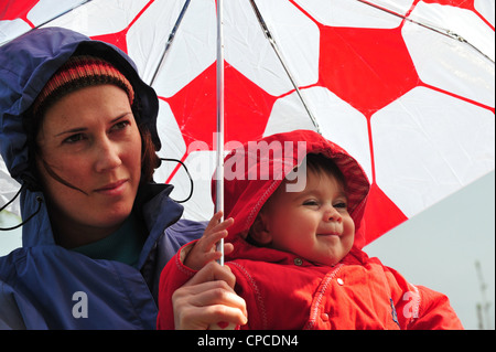 Mother and baby stand under an umbrella and look at the falling rain in a winter day . - Stock Photo