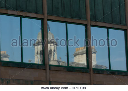 Reflection of old buildings in new shop window - Stock Photo