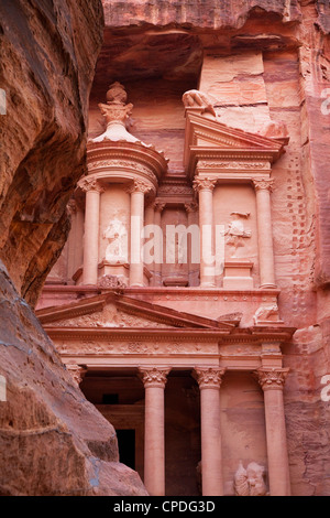 The facade of the Treasury (Al Khazneh) carved into the red rock with the Siq in the foreground, Petra, Jordan, - Stock Photo