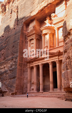 Tourist looking up at the facade of the Treasury (Al Khazneh) carved into the red rock at Petra, Jordan, Middle - Stock Photo
