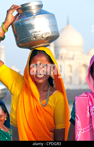 Woman carrying water pot on her head in front of the Taj Mahal, Agra, Uttar Pradesh state, India, Asia - Stock Photo