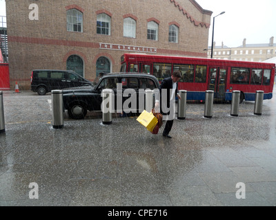 A man running between London taxi cab and St. Pancras Station with carrier bags in hail storm London England UK - Stock Photo