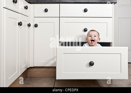 Smiling Baby Girl in Kitchen Drawer - Stock Photo