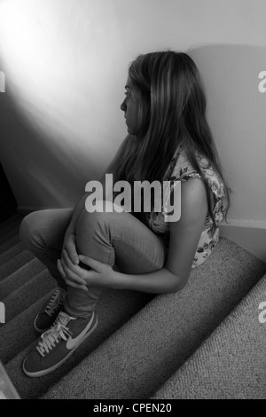 Young girl sitting on dark stairs back view - Stockfoto