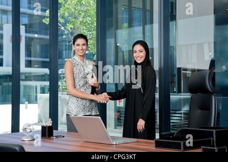 Two businesswomen shaking hands in office. - Stock Photo