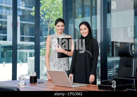 Two businesswomen standing in office, smiling. - Stock Photo