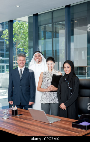 Portrait of business people standing in office, smiling. - Stock Photo