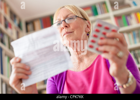 Elderly caucasian woman with medicine and reading drug prescription. Low angle view - Stock Photo