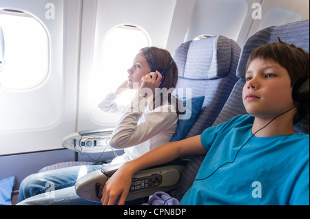 Children watching movie on airplane with headphones - Stock Photo