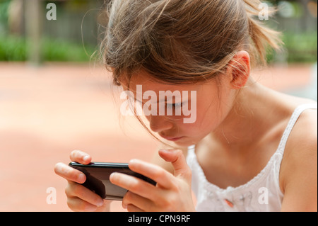 Girl playing with smartphone - Stock Photo