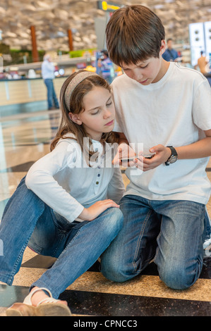 Brother playing with cell phone, sister watching with interest - Stock Photo