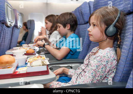 Girl watching movie on airplane, airline meal on tray table - Stock Photo