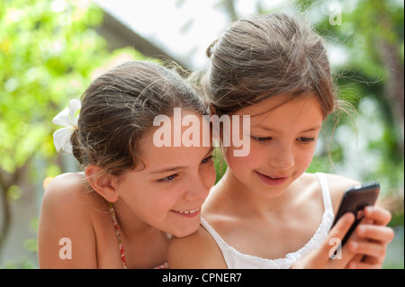 Sisters looking at cell phone together - Stock Photo