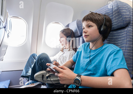 Boy using remote control to change channels on airplane - Stock Photo