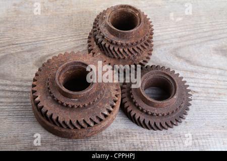 Rusty iron gear wheels on a unplaned boards - Stock Photo