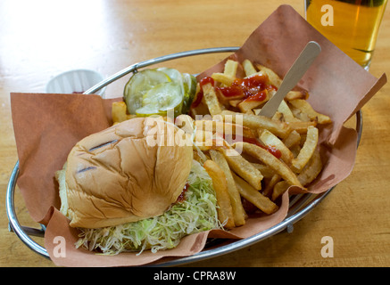 Cheeseburger and fries with lettuce, tomato and pickle with beer - Stock Photo