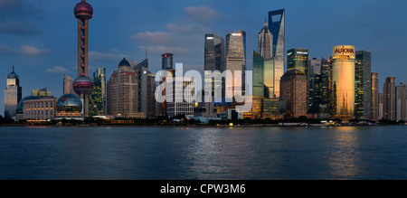 Panorama at dusk red glow on high rise financial towers and hotels in the Pudong east side of Shanghai China - Stock Photo