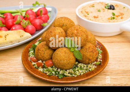 Middle Eastern treats, falafel sitting on a bed of tabbouleh, with hummus and radishes. - Stockfoto