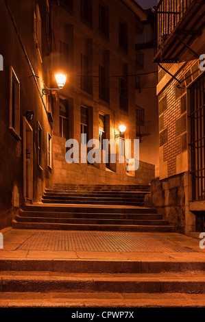 Narrow alley and steps illuminated by street lamps at night, Madrid, Spain - Stock Photo