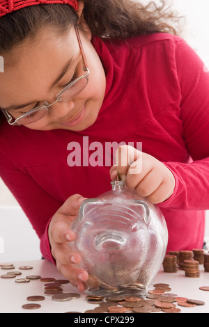 Young girl inserting coins in piggy bank - Stock Photo