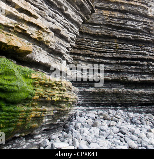 Textured Rocks byt seaside cove cave including limestone & pebbles - Stock Photo