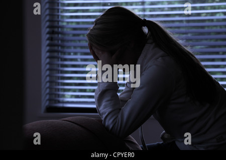 Profile of a girl with a ponytail, sitting hands covering her face. Silhouette. - Stock Photo